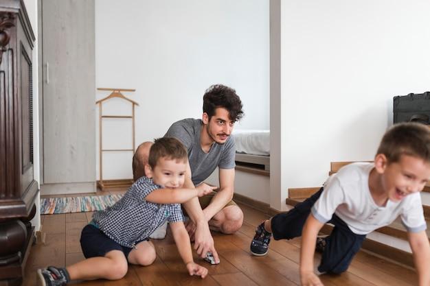 Uomo che gioca i suoi figli sul pavimento in legno a casa