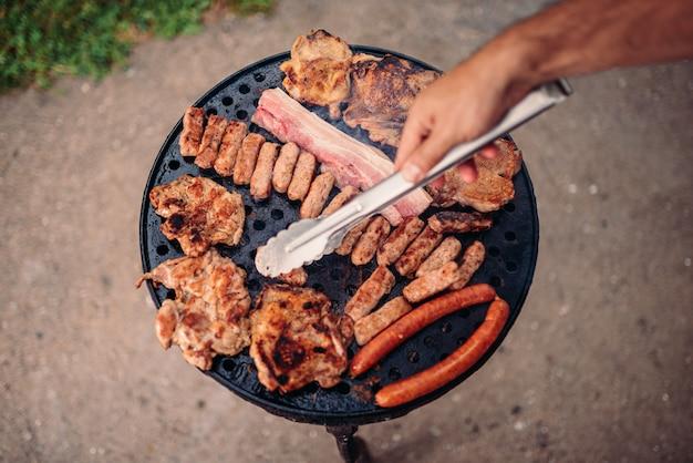 Uomo che griglia la carne sul barbecue