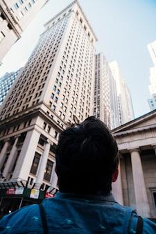 Uomo che guarda alti grattacieli
