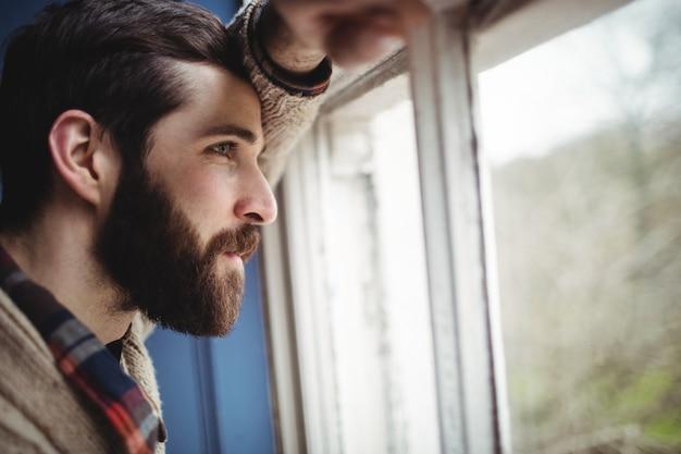 Uomo che guarda attraverso la finestra