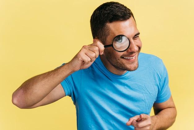 Uomo che guarda attraverso una lente d'ingrandimento