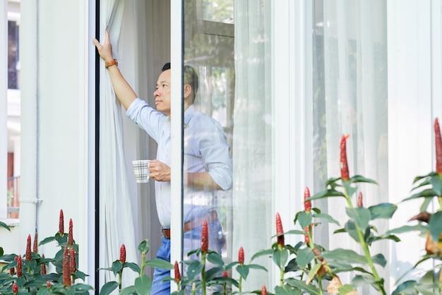 Uomo che guarda bella vista dalla finestra