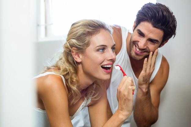 Uomo che guarda la donna mentre lavarsi i denti
