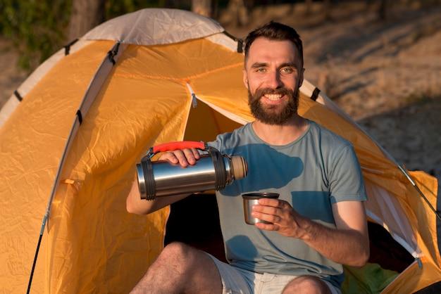 Uomo che guarda la macchina fotografica e versando il tè