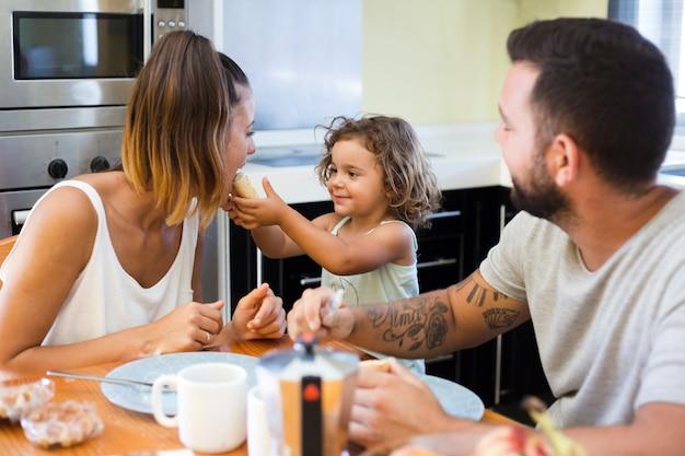 Uomo che guarda la ragazza che alimenta il pane a sua madre