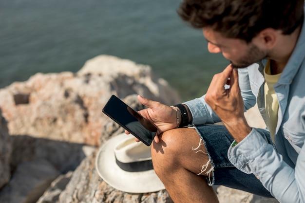 Uomo che guarda su smartphone in riva al mare