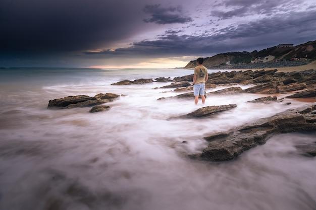 Uomo che guarda verso il mare mentre il mare colpisce gli scogli a bidart, paesi baschi.