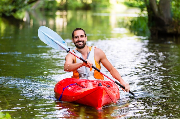 Uomo che guida con kayak sul fiume foresta