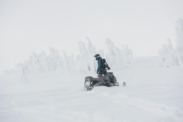 Uomo che guida in motoslitta nelle alpi innevate
