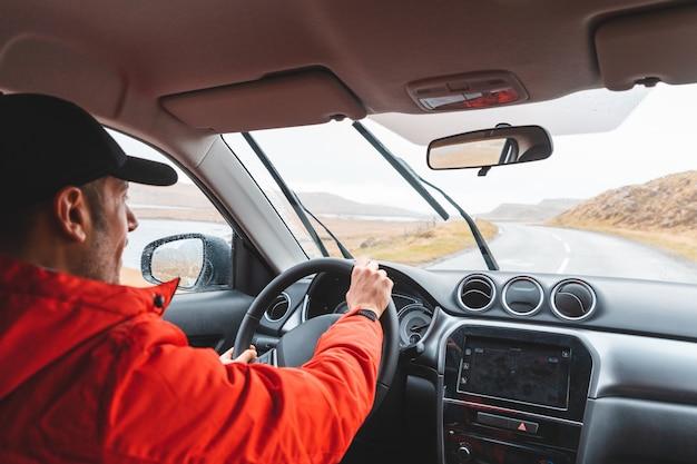 Uomo che guida l'automobile suv sulla strada costiera