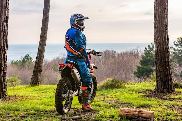 Uomo che guida un motocross in una tuta protettiva