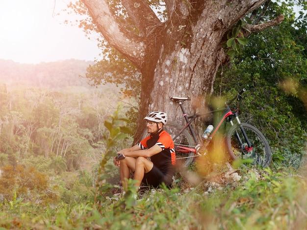 Uomo che guida una mountain bike nella foresta. si riposa, facendo una pausa si siede sotto l'albero.