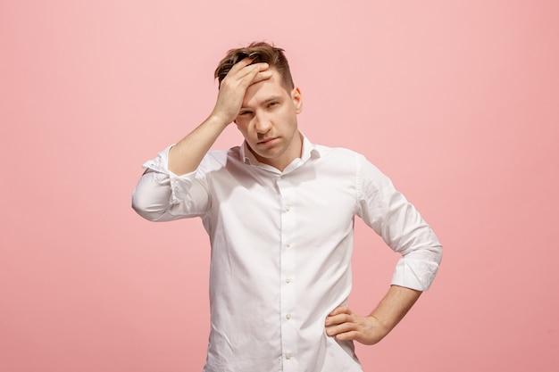 Uomo che ha mal di testa. isolato su muro rosa.