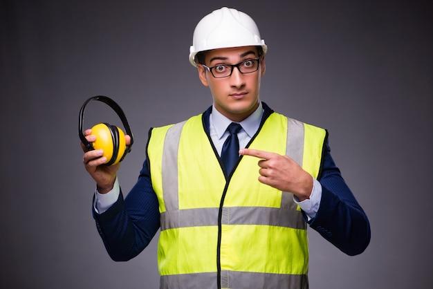 Uomo che indossa cappello duro e giubbotto di costruzione