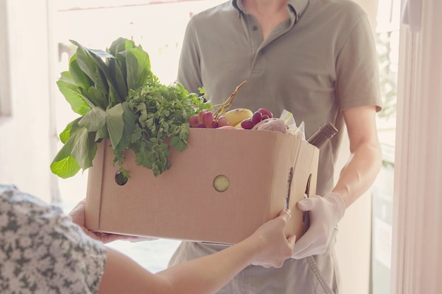 Uomo che indossa guanti a casa consegna scatola di cibo, volontario che tiene scatola di generi alimentari per donazione alla comunità