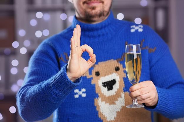 Uomo che indossa maglione di cervo blu caldo tenere in braccio champagne