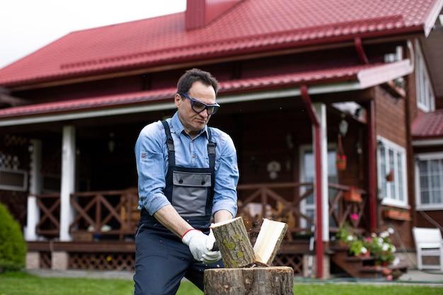 Uomo che indossa occhiali tagliare la legna su sfondo di una bella casa in legno