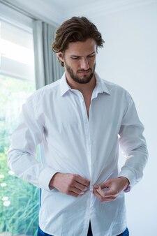 Uomo che indossa una camicia bianca in camera da letto