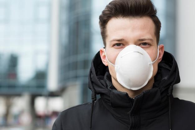 Uomo che indossa una maschera medica fuori