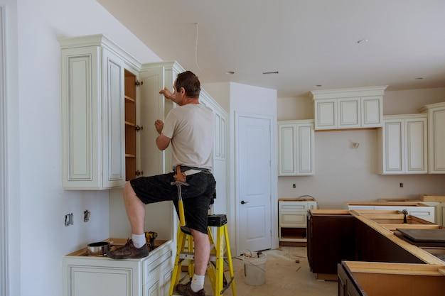 Uomo che installa la porta degli armadi da cucina