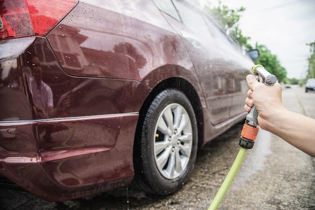 Uomo che lava auto usando shampoo e acqua
