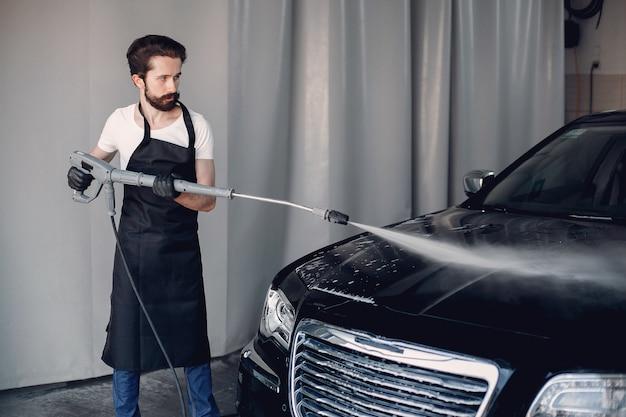 Uomo che lava la sua auto in un garage
