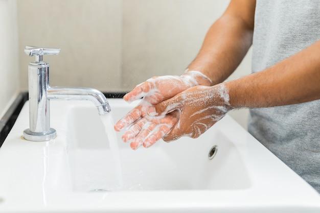 Uomo che lava le mani con il sapone.