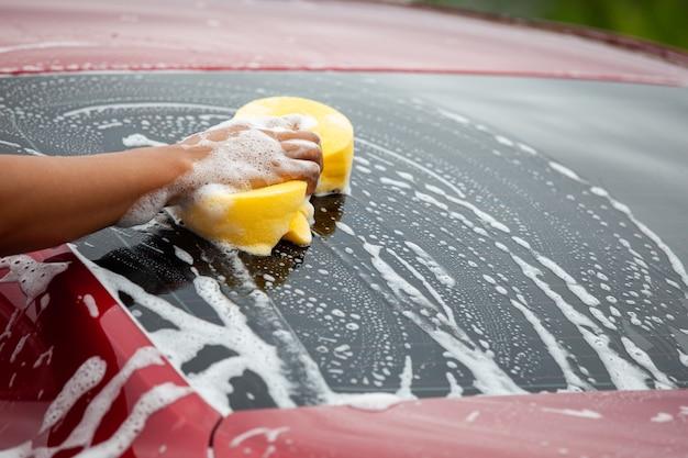 Uomo che lava macchina rossa con spugna e sapone