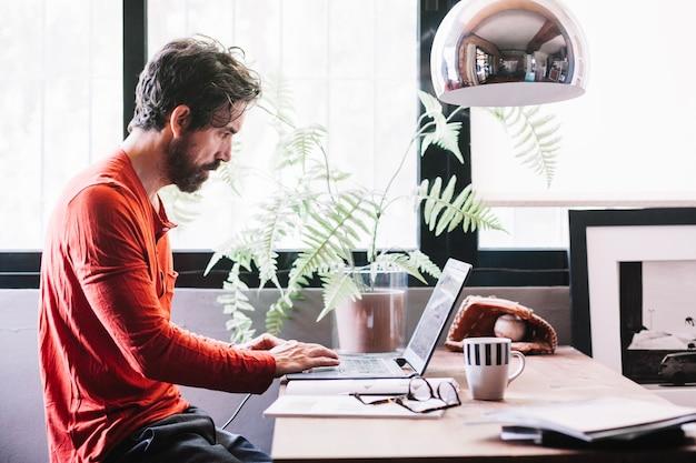 Uomo che lavora al computer portatile a casa