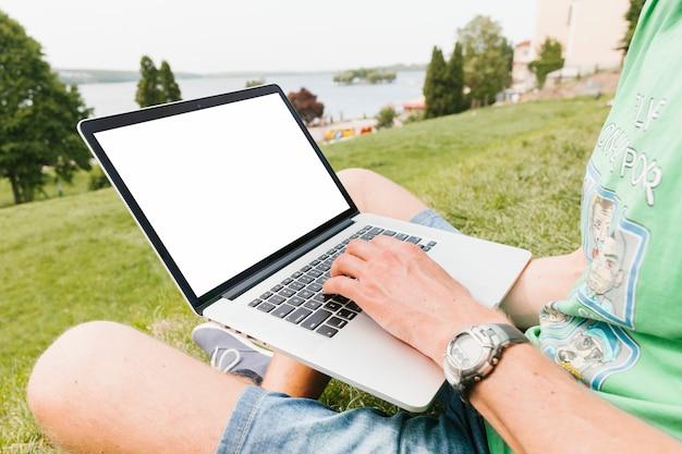 Uomo che lavora al computer portatile nel parco