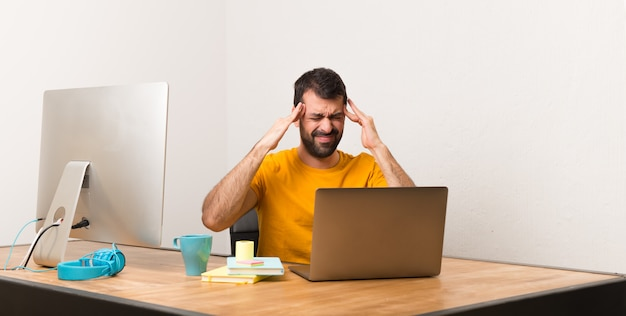 Uomo che lavora con laptot in un ufficio infelice e frustrato con qualcosa