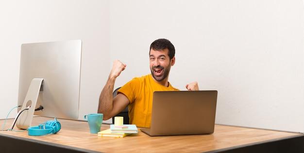 Uomo che lavora con laptot in un ufficio per celebrare una vittoria