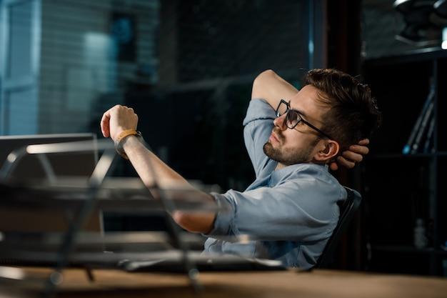 Uomo che lavora fino a tardi in ufficio, controllando il tempo