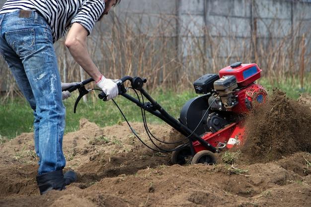 Uomo che lavora in giardino con la motozappa