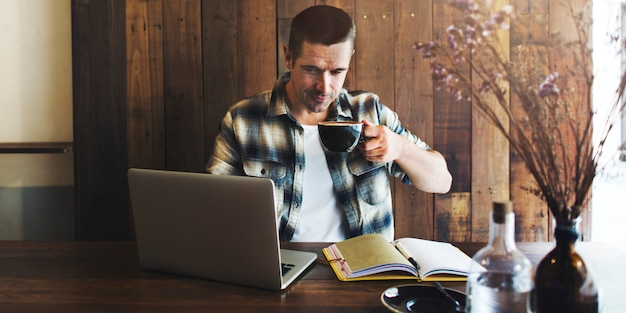Uomo che lavora sul suo computer portatile e bere caffè