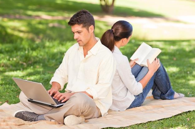Uomo che lavora sul suo computer portatile mentre sua moglie sta leggendo