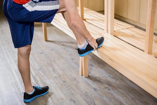 Uomo che lega il laccio delle scarpe nello spogliatoio in palestra