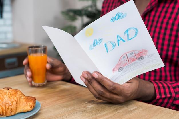 Uomo che legge la cartolina d'auguri con iscrizione di papà