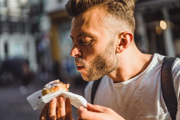 Uomo che mangia cialde olandesi in strada vicino al caffè. cibo di strada in olanda.