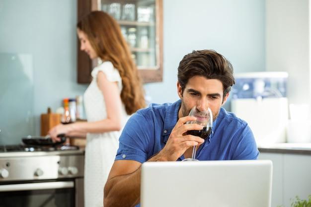 Uomo che mangia vino rosso e che per mezzo del computer portatile