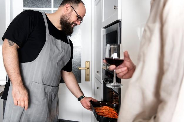 Uomo che mette la bistecca di salmone crudo nel forno