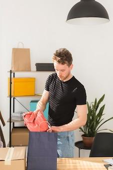 Uomo che mette la camicia in borsa