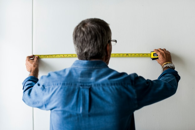 Uomo che misura il muro con un nastro di misurazione