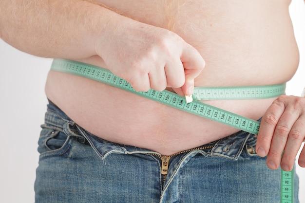 Uomo che misura la sua pancia grassa con nastro adesivo di misurazione