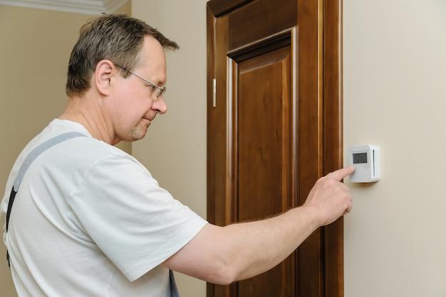 Uomo che modifica le impostazioni di un termostato