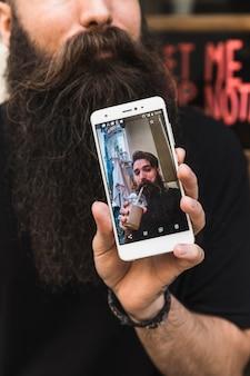 Uomo che mostra alta fotografia sullo schermo del telefono intelligente