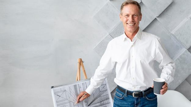Uomo che mostra i piani architettonici con lo spazio della copia