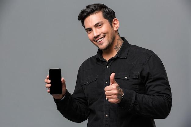 Uomo che mostra i pollici in su e la visualizzazione del telefono.