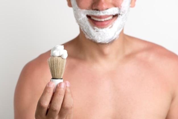Uomo che mostra il pennello da barba con schiuma durante la rasatura