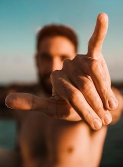 Uomo che mostra il segno della mano di shaka